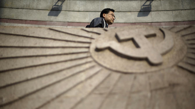 A man walks past a wall engraved with the insignia of the Chinese Communist Party on Tuesday, Nov. 6, 2012 in Shanghai, China. The party will hold its 18th National Congress on Thursday, Nov. 8, 2012 in Beijing. The once-a-decade event will install new leadership to run the world's second largest economy and newly assertive global power. (AP Photo/Eugene Hoshiko)