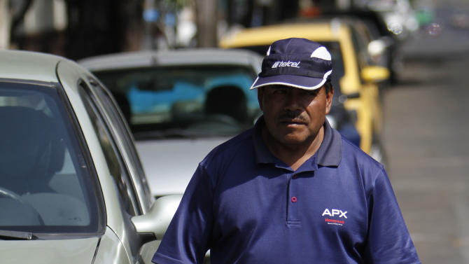 "A man who works as an unofficial parking attendant, known as a ""franelero,"" walks past cars he guards in the Roma neighborhood of Mexico City, Saturday, Jan. 19, 2013. Here and in other well-to-do areas of traffic-choked Mexico City, authorities are trying to take back the streets by installing parking meters. Often the only option is to pay the ad hoc attendants, known as ""franeleros"" for the rags - ""franelas"" - they use to signal cars in and out of parking spaces they have commandeered. (AP Photo/Marco Ugarte)"