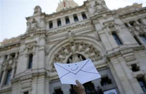 An anti-eviction activist holds an envelope in front of Madrid's Town Hall