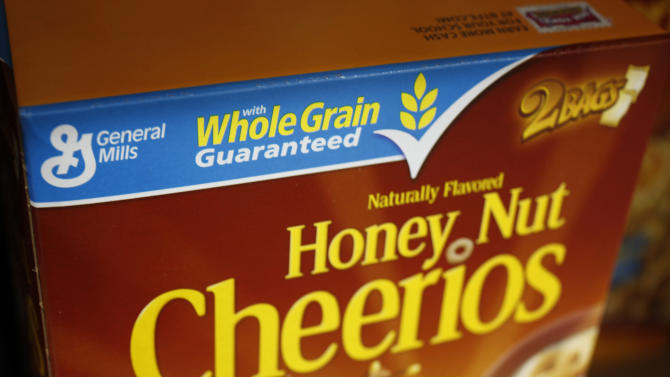 FILE - In this Dec. 8, 2009 photo, a box of Honey Nut Cheerios is seen on display at Costco in Mountain View, Calif. The nation's largest food companies say they will cut back on marketing unhealthier foods to children, proposing their own set of advertising standards after rejecting similar guidelines proposed by the federal government. The industry guidelines for children's' cereals, for example, would allow them to be advertised if they have around 10 grams of sugar a serving, while the formula used by the government would discourage advertising for cereals that have 8 grams of sugars in an equivalent serving. That would mean General Mills would still be able to advertise Honey Nut Cheerios cereal under the industry guidelines but would be discouraged under the voluntary government guidelines. (AP Photo/Paul Sakuma, File)