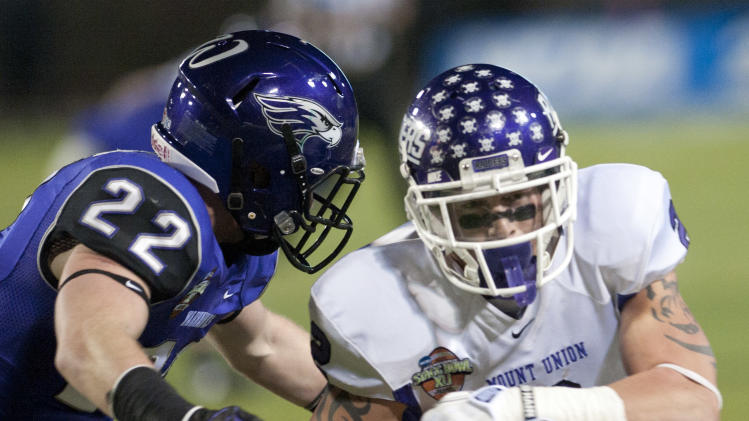 Mount Union's Luke Meacham gains yards against Wisconsin-Whitewater's Andrew Keister (22) during the first half of the NCAA Division III championship college football game at Salem Stadium in Salem, Va., Friday, Dec. 20, 2013. (AP Photo/Don Petersen)