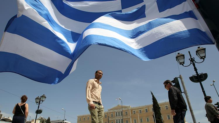 The Greek Parliament is seen behind country's flag in Athens, Friday, April 20, 2012. Polls indicate that Greece's majority Socialists are trailing their main conservative rivals by up to 7 percentage points nearly two weeks before crucial national elections. Voting is scheduled for Sunday, May 6. (AP Photo/Thanassis Stavrakis)