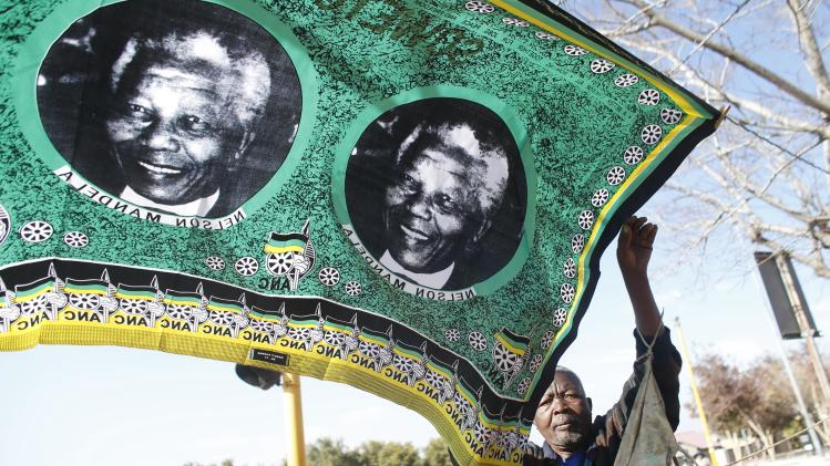 """A souvenir vendor set up his street shop with scarves showing portraits of former South African President Nelson Mandela near the Hector Peterson Museum in Soweto, Saturday June 29, 2013. The White House issued a statement Saturday that President Barack Obama plans to visit privately with relatives of former South African President Nelson Mandela, but doesn't intend to see the critically ill anti-apartheid activist he has called a """"personal hero."""" (AP Photo/Markus Schreiber)"""