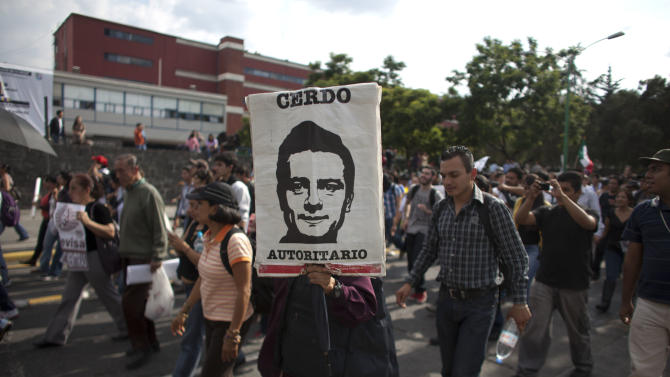 """A demonstrator holds an image depicting Mexico's President-elect Enrique Pena Nieto, of the Institutional Revolutionary Party (PRI), that reads in Spanish """"Authoritarian pig"""" during a protest against the official presidential election results in Mexico City, Friday, Aug. 31, 2012.  On Friday, the Federal Electoral Tribunal declared Pena Nieto won the majority of votes in last July's presidential election, and he will be sworn-in on Dec. 1. (AP Photo/Alexandre Meneghini)"""
