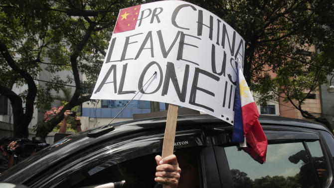 A protester displays a placard from a car during a rally outside the Chinese consulate Friday, May 11, 2012 in Manila's financial district of Makati, Philippines. The Philippines and China are in a standoff over Scarborough Shoal which began early April after the Philippine navy accused Chinese boats of illegally fishing in the area. The protesters called on the Chinese government to pull out its vessels in the area and asserted that the shoal is part of Philippine territory. (AP Photo/Pat Roque)