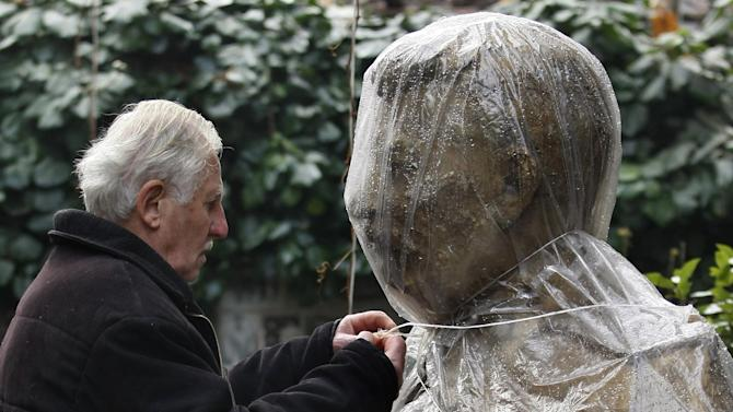Ushangi Davitashvili removes plastic wrap from the bust of Soviet dictator Josef Stalin that stands in the courtyard of his apartment building in the Georgian capital, Tbilisi, Friday, Dec. 21, 2012. Stalin was born in Georgia in 1879 and led the Soviet Union through decades of totalitarian reforms and political purges. (AP Photo/Shakh Aivazov)