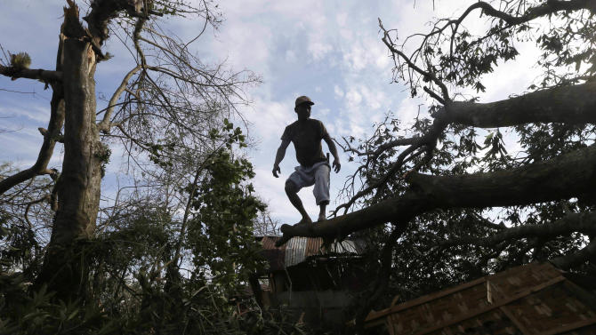 A resident balances himself after cutting branches of a tree that fell on his house at the height of Typhoon Bopha in Montevista, Compostela Valley in southern Philippines Thursday Dec. 6, 2012. The powerful typhoon that washed away emergency shelters, a military camp and possibly entire families in the southern Philippines has killed hundreds of people with nearly 400 missing, authorities said Thursday. (AP Photo/Bullit Marquez)