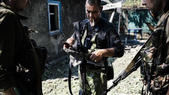 A pro-Russian gunman holds a piece of shrapnel from a rocket after shelling in downtown Donetsk on August 22, 2014