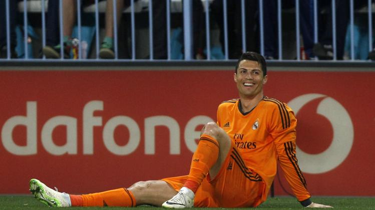 Real Madrid's Cristiano Ronaldo smiles after falling on the pitch during their Spanish First Division soccer match against Malaga in Malaga
