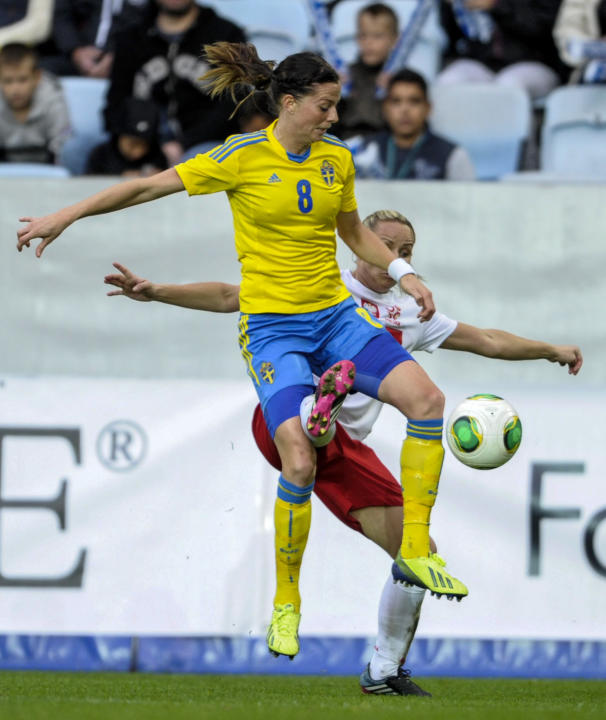 Sweden's Lotta Schelin, front, vies for the ball with Poland's Patrycja Pozerska, back, during the ladies' football World Championships qualification match at Swedbank Stadium in Malmo, Sweden, Saturd