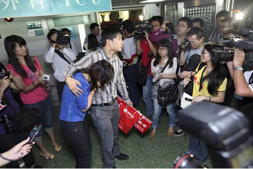 In this photo taken Tuesday Oct. 18, 2011, journalists surround the unidentified parents of a two-year-old girl identified as Wang Yue in a hospital in Guangzhou in south China's Guangdong province.  A video showing Wang Yue being struck twice by vans and then ignored by passers-by is sparking outrage in China and prompting soul-searching over why people didn't help the child.  (AP Photo) CHINA OUT