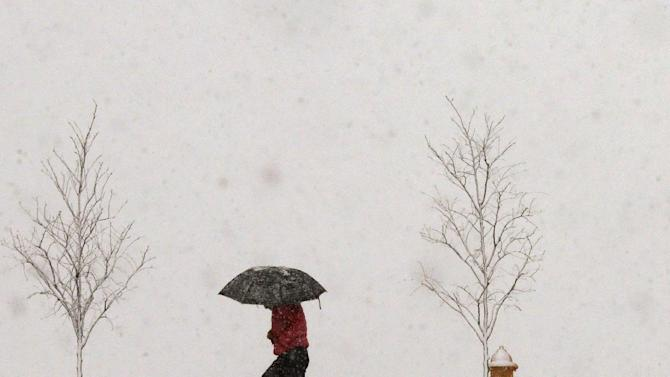 A person walks along Jayhawk Boulevard with an umbrella as snow from a winter storm begins to fall in Lawrence, Kan., Saturday, March 23, 2013. (AP Photo/Orlin Wagner)