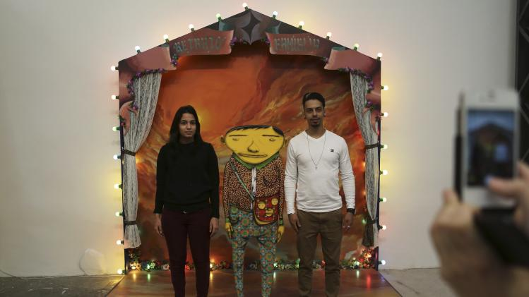 "Visitors pose next to an artwork by Brazilian artists and twin brothers, who go by the name ""Os Gemeos"", during their exhibition ""Opera of the Moon"" in Sao Paulo"