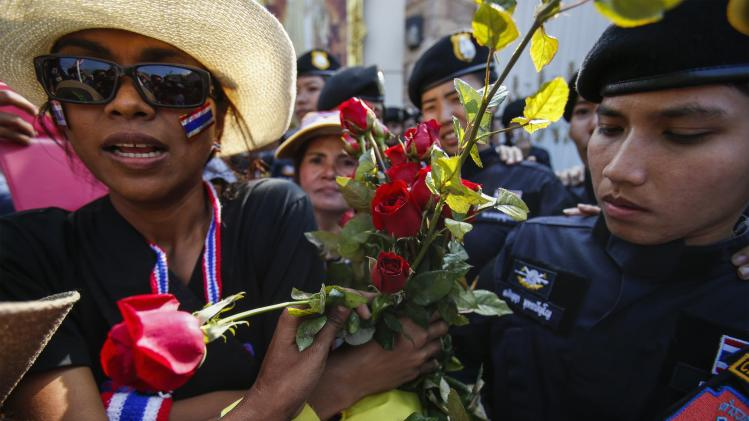 An anti-government protester gives flowers to riot police during mass rally outside house of PM Yingluck in Bangkok