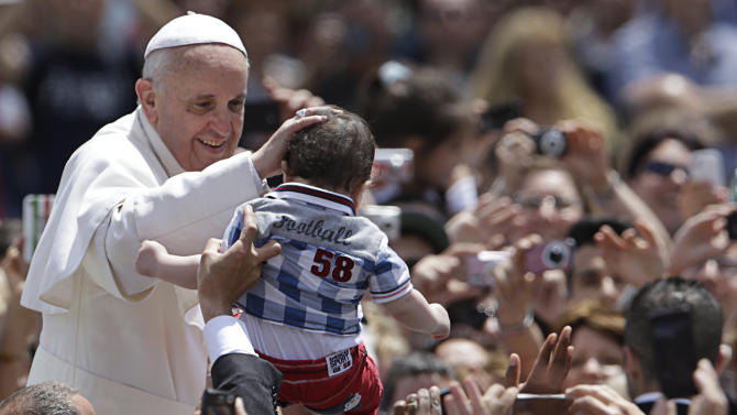 Pope Francis caresses a child in St. Peter Square at the Vatican, after celebrating a Pentecost mass, Sunday, May 19, 2013.(AP Photo/Andrew Medichini)
