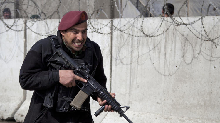 An Afghan Army soldier runs to take up position outside the Afghan Defense Ministry after a suicide bomber on a bicycle struck outside the ministry, killing at least nine Afghan civilians as U.S. Defense Secretary Chuck Hagel visited Kabul, Afghanistan, Saturday, March 9, 2013.  (AP Photo/Anja Niedringhaus)