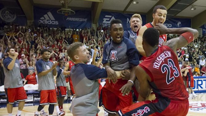 Arizona players rush the court after defeating San Diego State 61-59 in an NCAA college basketball game to win the Maui Invitational on Wednesday, Nov. 26, 2014, in Lahaina, Hawaii. (AP Photo/Eugene Tanner)