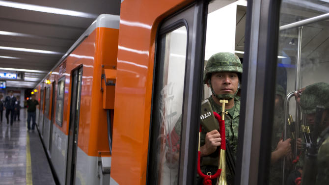 Subway doors close on members of an army marching band traveling back to their camp, after an Independence Day parade by Mexico's Armed Forces, in the Zocalo, in central Mexico City, Mexico, Tuesday, Sept. 16, 2014. Mexico is marking the 204th anniversary of its independence from Spain. (AP Photo/Rebecca Blackwell)
