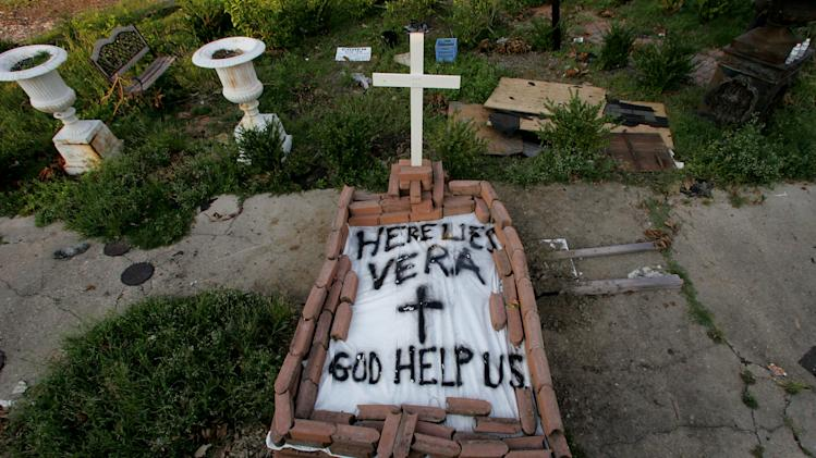 "FILE - In this Sept. 4, 2005 file photo, a makeshift tomb at a New Orleans street corner conceals a body that had been lying on the sidewalk for days in the wake of Hurricane Katrina. The message reads, ""Here lies Vera. God Help Us."" (AP Photo/Dave Martin)"