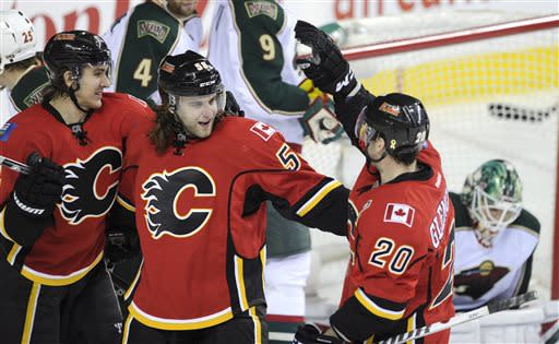 Calgary Flames' Ben Hanowski, center, celebrates his first NHL goal with Curtis Glencross, right, and Mikael Backlund, from Sweden, during the third period of an NHL hockey game against the Minnesota Wilde in Calgary, Alberta, Monday, April 15, 2013