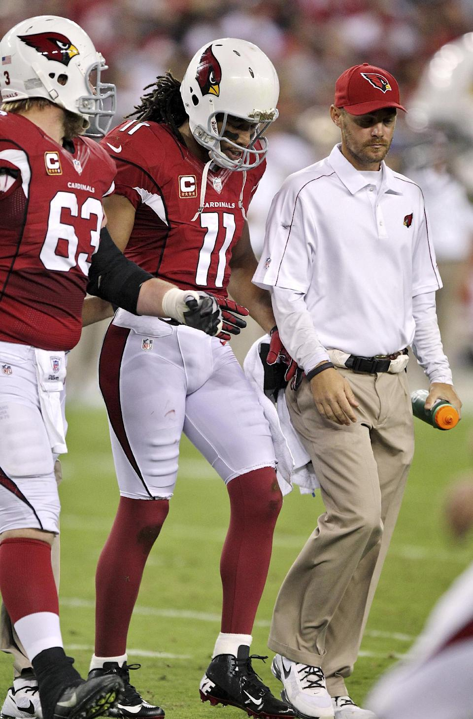 Arizona Cardinals wide receiver Larry Fitzgerald (11) leaves the field after being hurt during the first half of an NFL football game against the San Francisco 49ers, Monday, Oct. 29, 2012, in Glendale, Ariz. At left is Lyle Sendlein (63). (AP Photo/Paul Connors)