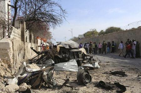 People look at the scene of a suicide attack next to the gate of the Presidential Palace in Mogadishu