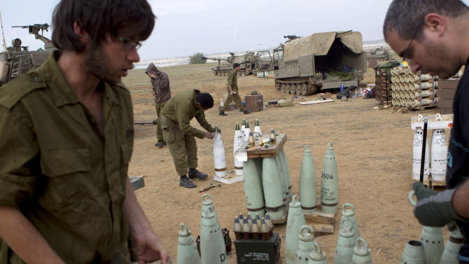 Israeli reserve soldiers remove detonators from shells in a 155 mm artillery position near Israel Gaza Border, southern Israel, Thursday, Nov. 22, 2012. A cease-fire agreement between Israel and the Gaza Strip's Hamas rulers took effect Wednesday night, bringing an end to eight days of the fiercest fighting in years and possibly signaling a new era of relations between the bitter enemies. (AP Photo/Ariel Schalit)