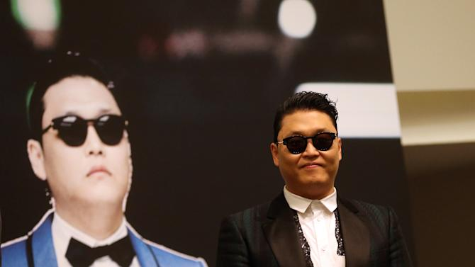 "FILE - In this Dec. 1, 2012 file photo, South Korean rapper PSY, who gained popularity from his famous song ""Gangnam Style,"" gives a press conference prior to his concert at the Marina Bay Sands in Singapore. President Barack Obama still intends to attend a charity concert where PSY is scheduled to perform after reports the South Korean rapper participated in anti-American protests several years ago. (AP Photo/Wong Maye-E, File)"