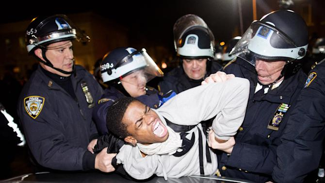 """Police officers arrest a demonstrator during a march after a vigil held for Kimani """"Kiki"""" Gray in the East Flatbush neighborhood of Brooklyn, Wednesday, March 13, 2013, in New York. The 16-year-old was shot to death on a Brooklyn street last Saturday night by plainclothes police officers who claim the youth pointed a .38-caliber revolver at them. (AP Photo/John Minchillo)"""