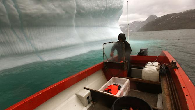 In this July 26, 2011 photo, a Greenlandic Inuit hunter and fisherman steers his boat past a melting iceberg, along a fjord leading away from the edge of the Greenland ice sheet, near Nuuk, Greenland. (AP Photo/Brennan Linsley)