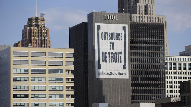 In this July 12, 2013, photo an Outsource to Detroit banner from Galaxe.Solutions is seen on a Detroit building. State-appointed emergency manager Kevyn Orr on Thursday, July 18, 2013, asked a federal judge permission to place Detroit into Chapter 9 bankruptcy protection.. (AP Photo/Carlos Osorio)