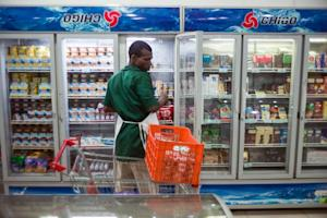 An employee of a supermarket stocks shelves in Bangui,…