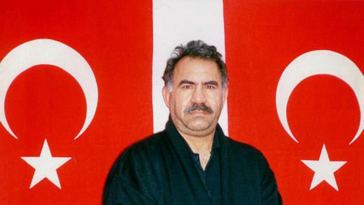 "FILE - In this file photo provided by the Turkish Intelligence Service on Feb. 18, 1999,  Kurdish rebel leader Abdullah Ocalan poses in front of Turkish flags before being interrogated by Turkish officials at the prison-island of Imrali , Turkey. Ocalan said Monday, March 18, 2013 that peace talks with Turkey are making ""positive progress"" and that he plans to make a ""historic"" announcement to coincide with a Kurdish spring festival. (AP Photo/Turkish Intelligence Service, File)"