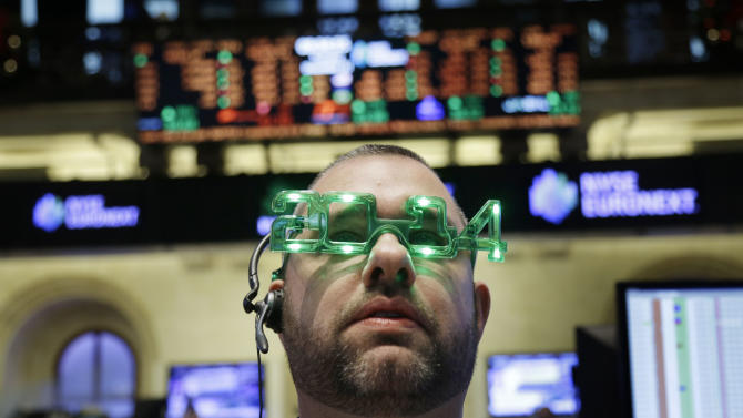 FILE - In this Tuesday, Dec. 31, 2013, file photo, a trader wears glasses celebrating the new year while working on the floor at the New York Stock Exchange in New York. U.S. stock futures are under pressure Jan. 2, 2014, after markets in 2013 saw their biggest gains in nearly two decades. (AP Photo/Seth Wenig, File)