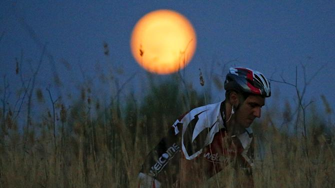 A cyclist rides his mountain bike as a full moon, known as the Blue Moon, rises in a park in Rome