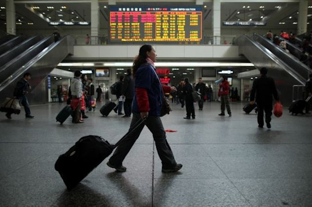 A woman pulls her luggage past an electronic information board at Guangzhou train station on January 30, 2011