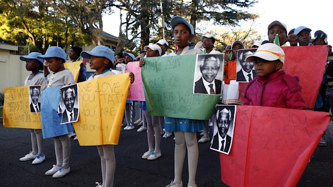 Soweto African Kids hold posters and prints of Mandela and get well messages outside the home of the former President Nelson Mandela in Johannesburg, South Africa, Saturday, June 15, 2013. Mandela, remains in the hospital for a seventh day. The 94-year-old was hospitalized on Saturday for a recurring lung infection. (AP Photo/Themba Hadebe)