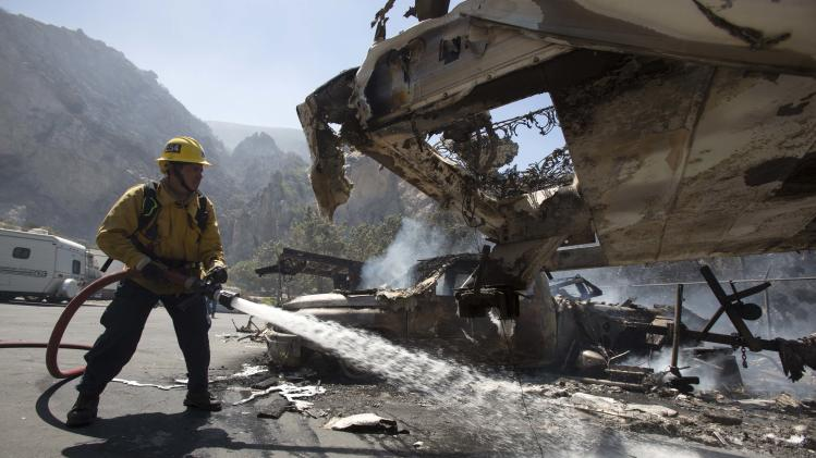 A firefighter puts out a fire while the mobile homes are burning after after a blaze broke out during morning rush hour along U.S. 101 in the Camarillo area about 50 miles west of Los Angeles, May. 2, 2013, in Camarillo, Calif.  A wildfire fanned by gusty Santa Ana winds raged along the fringes of Southern California communities on Thursday, forcing evacuation of homes and a university while setting recreational vehicles ablaze. (AP Photo/Ringo H.W. Chiu)
