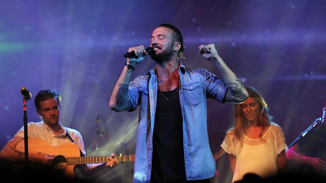 In this July 14, 2013 photo, Pastor Carl Lentz, center, leads a Hillsong NYC Church service at Irving Plaza in New York. With his half-shaved head, jeans and tattoos, Pastor Carl Lentz doesn't look like the typical religious leader. But with its concert-like atmosphere and appeal to a younger demographic, his congregation, Hillsong NYC, is one of the fastest growing evangelical churches in the city. (AP Photo/Tina Fineberg)