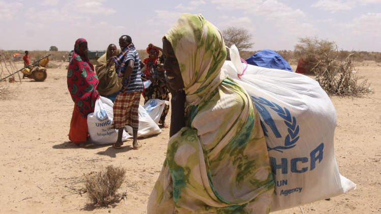 Southern Somali people carry essential food aid donations from the UNHCR, as they make their way to their refugee camp in Dollow, Somalia, Tuesday. Aug. 30, 2011.  Despite the drought and famine, refugees in Somalia are celebrating the Muslim holiday of Eid al-Fitr with the food rations distributed by aid agencies for their survival. (AP Photo/Khalil Senosi)