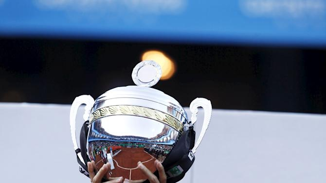 Federer of Switzerland celebrates with the trophy after his victory against Uruguay's Cuevasin