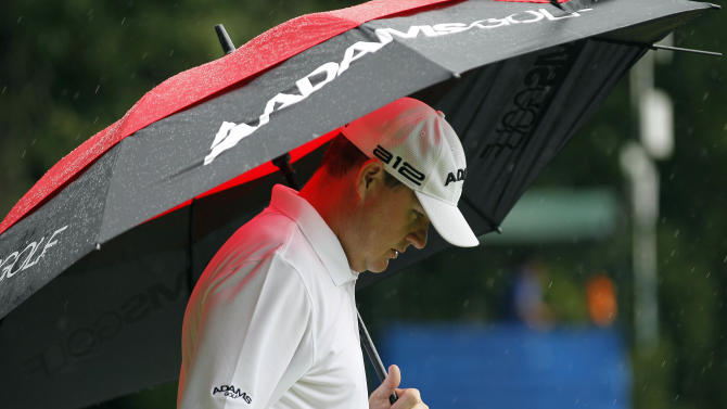 Chad Campbell keeps away from the rain during the final round of the Wyndham Championship golf tournament in Greensboro, N.C., Sunday, Aug. 19, 2012. (AP Photo/Gerry Broome)