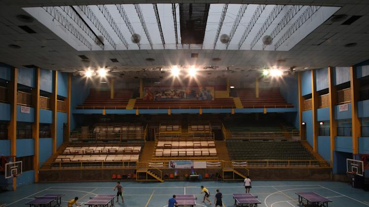 In this May 29, 2013 photo, students play ping-pong at the indoor stadium Estadio Victor Jara where spare beds for the homeless are stored in the seating area in Santiago, Chile. Political prisoners, mostly university students, were held in these same stadium seats in Sept. 1973 after the bloody coup that ousted President Salvador Allende. Those who survived were later transferred to another detention center. Today the stadium is Chile's largest homeless shelter, housing about 500 people per day during the biting Chilean winter. (AP Photo/Brittany Peterson)