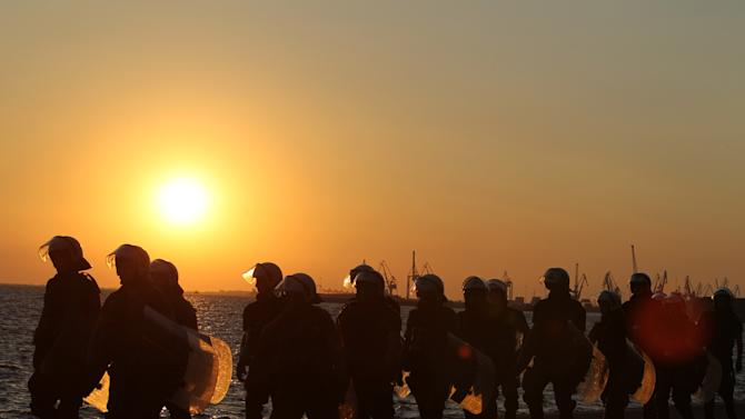 Riot police follow protesters as the sun sets in the northern Greek port city of Thessaloniki, Saturday, Sept. 8, 2012. Greek Prime Minister Antonis Samaras says the final round of austerity measures contains painful and unjust cuts but is necessary to restore Greece's credibility and continue to receive funding from creditors. (AP Photo/Thanassis Stavrakis)