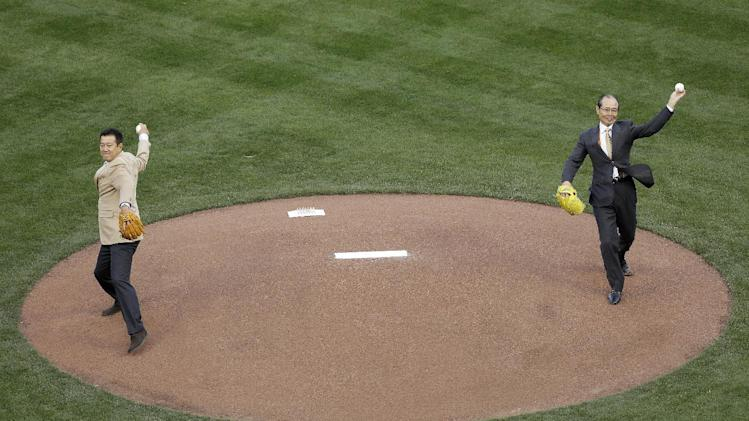 Former baseball players Tatsunori Hara, left, and Sadaharu Oh throw out the ceremonial first pitch before a semifinal game of the World Baseball Classic between Japan and Puerto Rico in San Francisco, Sunday, March 17, 2013. (AP Photo/Jeff Chiu)