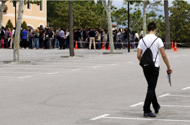A man walks to join a line to submit his resume during an employment fair in La Roca Village