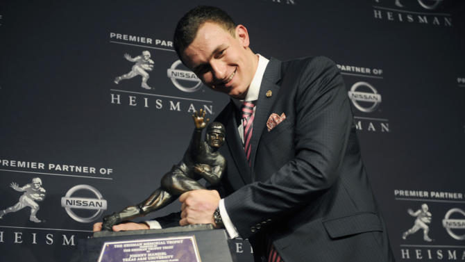 Texas A&M quarterback Johnny Manziel poses with the Heisman Trophy after becoming the first freshman to win the award, Saturday, Dec. 8, 2012, in New York. (AP Photo/Henny Ray Abrams)