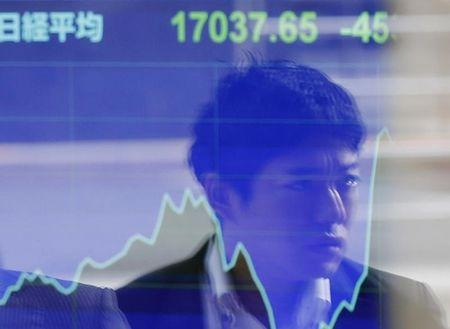 A passer-by is reflected on an electronic board showing Japan's Nikkei stock average at a brokerage in Tokyo