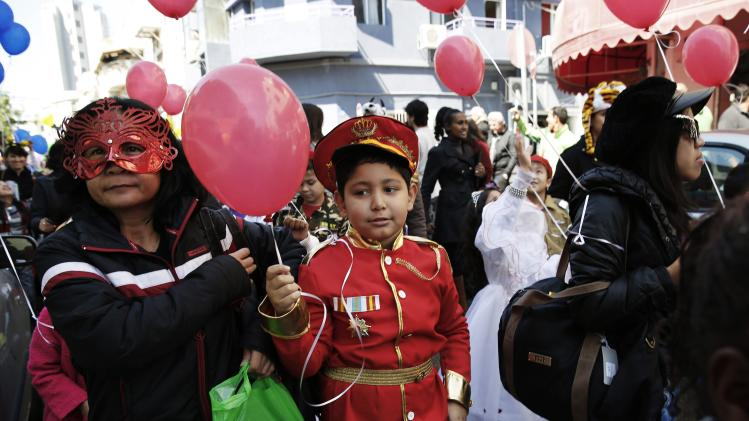 Children and their parents wear costumes as they take part in a parade celebrating the Jewish holiday of Purim outside the Bialik Rogozin school in south Tel Aviv