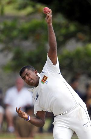 Sri Lankan cricketer Rangara Herath bowls during the first day of the first test cricket match between Australia and Sri Lanka in Galle, about 80 kilometers (50 miles) south of Colombo, Sri Lanka,  Wednesday, Aug. 31, 2011. (AP Photo/Gemunu Amarasinghe)